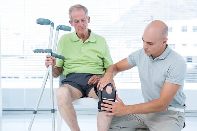 Lekarz badając jego kolano pacjenta