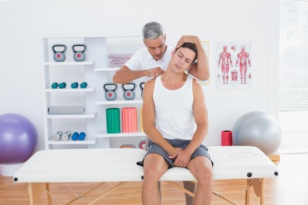 Lekarz badając jego szyi pacjenta