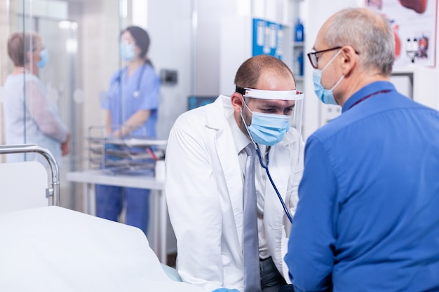 Lekarz badający bicie serca starszego pacjenta podczas konsultacji stetoskopem i noszący maskę przeciw covid-19
