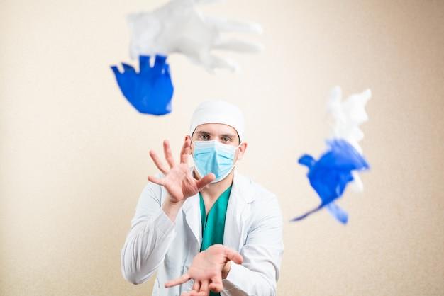 Lekarz bawi się i rzuca rękawiczki. na jasnym tle. zdjęcie wysokiej jakości