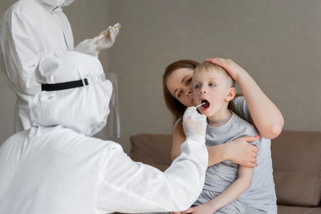 Lekarz bierze wacik z ust dziecka, aby przeanalizować ślinę, błonę śluzową do badań dna, covid-19, w celu ustalenia lub obecności wirusa, epidemii sars-cov-2, koncepcji koronawirusa