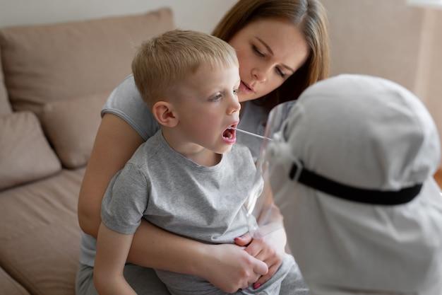 Lekarz bierze wacik z ust dziecka, aby przeanalizować ślinę pod kątem covid-19