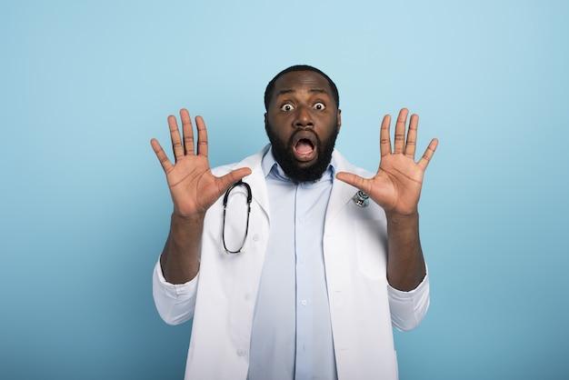 Lekarz boi się ataku wirusa codiv19. niebieska ściana