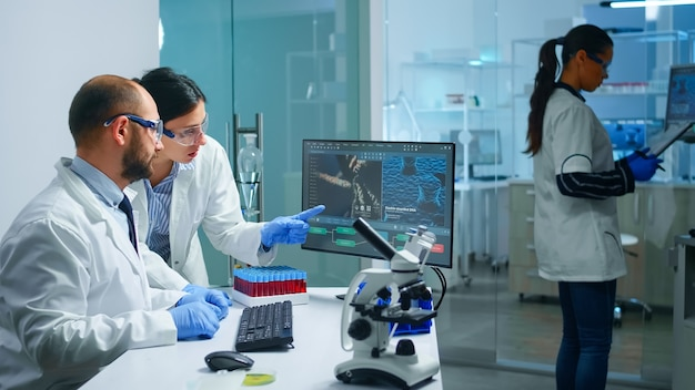 Lekarz chemik wyjaśniający współpracownikom rozwój szczepionek, mutacje dna pracujące w wyposażonym laboratorium