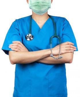 Lekarz chirurg nosi mundur koszuli w kolorze niebieskim i zieloną maskę na twarz. stojak lekarza z rękami skrzyżowanymi i ręka trzyma stetoskop. pracownik służby zdrowia.