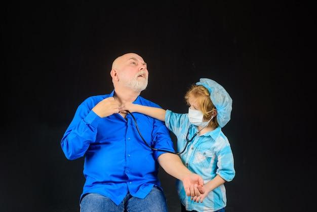 Lekarz chłopiec lekarski bawi się z leczeniem dziadkiem leczenie domowe lekarz gra dzieciak bawi się z lekarzem