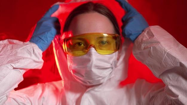 Lekarz chorób zakaźnych zakłada ubranie ochronne i maskę do pracy z zakażonymi pacjentami