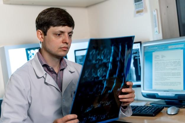 Lekarz czyta film rentgenowski. selektywne skupienie. portret radiologa w miejscu pracy.