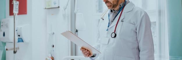Lekarz czyta kartę medyczną pacjenta z koronawirusem