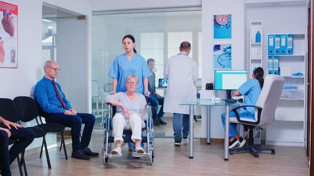 Lekarz dający radiografii pielęgniarki chorego pacjenta. asystent medyczny i nieważna starsza kobieta na wózku inwalidzkim. stary człowiek w poczekalni kliniki. system opieki zdrowotnej i konsultacje lekarskie