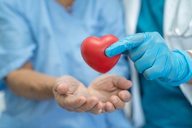 Lekarz daje czerwone serce pacjentce azjatyckiej starszej kobiety