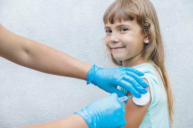 Lekarz daje dziecku zastrzyk w ramię