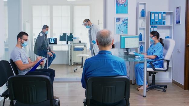 Lekarz daje pielęgniarka radiografia pacjenta podczas kończenia badania chorego w jego gabinecie. asystent z maską na twarz przeciwko covid-19 pchający niepełnosprawną kobietę na wózku inwalidzkim przez poczekalnię.