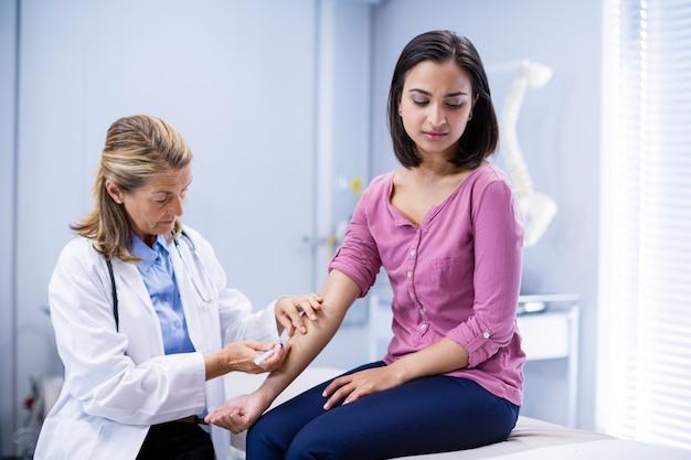 Lekarz daje zastrzyk pacjentowi