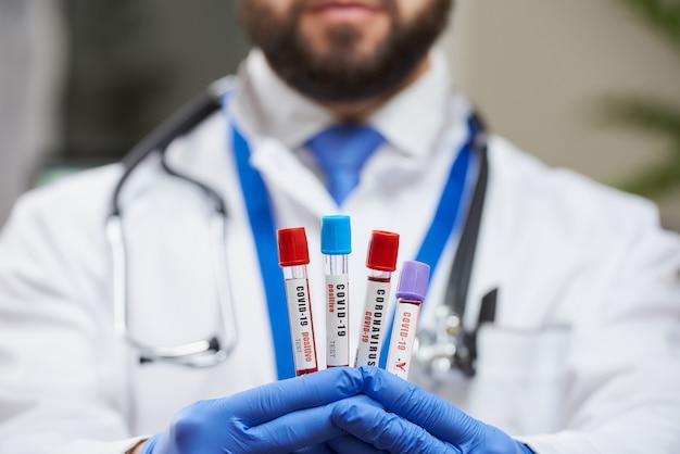 Lekarz demonstrujący w swoich rękach ławkę testów rurek krwi koronawirusa.