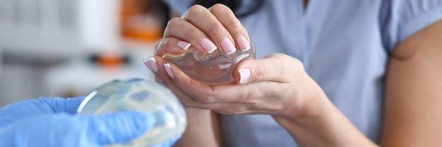 Lekarz demonstruje kobietom silikonowe implanty piersi