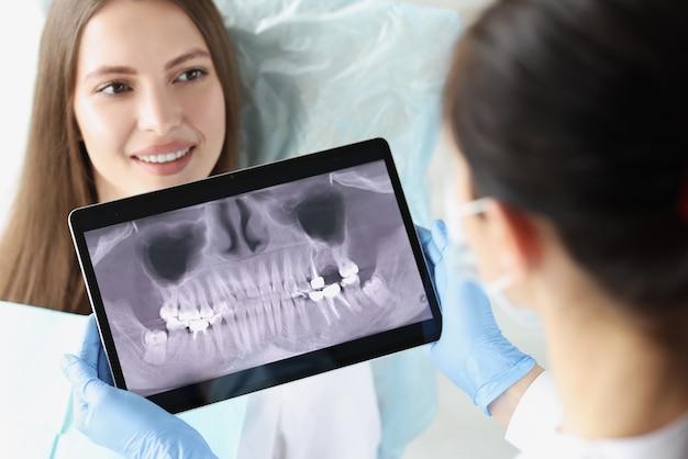 Lekarz dentysta bada prześwietlenie szczęki pacjentki