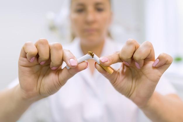 Lekarz dentysta łamie papierosa