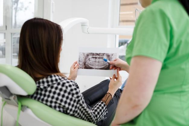Lekarz dentysta pokazuje swojemu pacjentowi prześwietlenie jamy ustnej