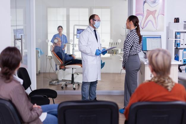 Lekarz dentysta przesłuchuje kobietę i robi notatki w schowku stojącym w poczekalni