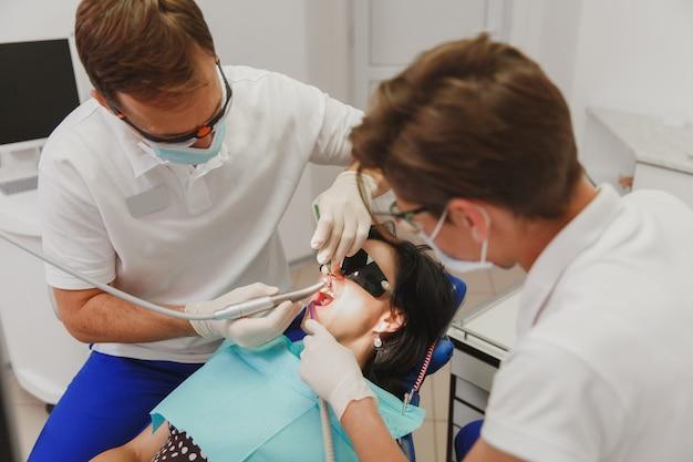 Lekarz dentysta z asystentką pomaga leczyć zęby pacjentki w klinice w gabinecie