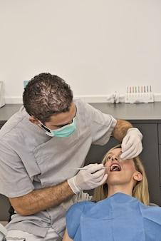 Lekarz dentysta z niebieską maską sprawdza stan jamy ustnej pacjentki leżącej w fotelu nowoczesnej kliniki dentystycznej.