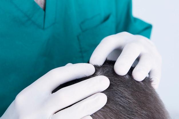 Lekarz dermatolog w rękawiczkach bada głowę dziecka