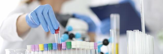 Lekarz diagnostyki laboratoryjnej trzyma szklaną probówkę w gumowej rękawicy zbliżenie. badania pcr dotyczące koncepcji covid 19.
