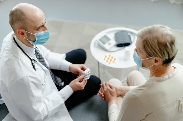 Lekarz domowy wyjaśnia pacjentowi zasady przyjmowania leków