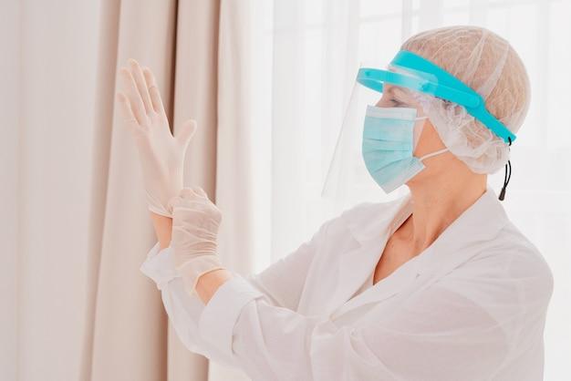 Lekarz dopasowuje rękawiczki, aby chronić się przed wirusem covid-19