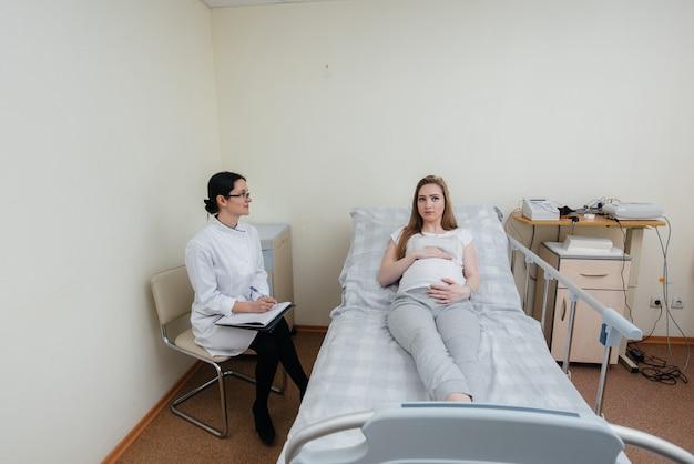 Lekarz doradza i służy młodej ciężarnej dziewczynie w klinice medycznej. badanie lekarskie