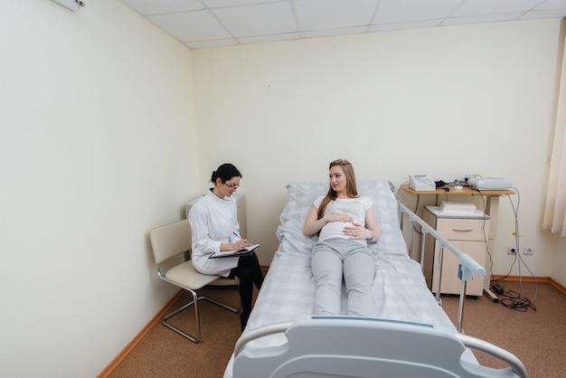 Lekarz doradza i służy młodej ciężarnej dziewczynie w klinice medycznej. badanie lekarskie.