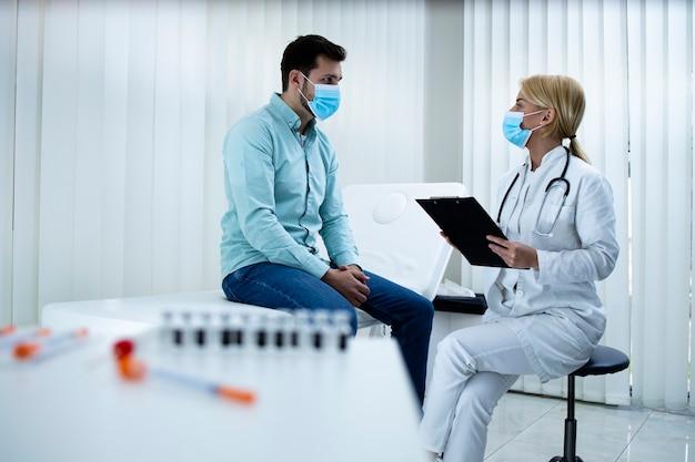 Lekarz doradza młodemu człowiekowi, jak zachować zdrowie podczas pandemii wirusa koronowego.