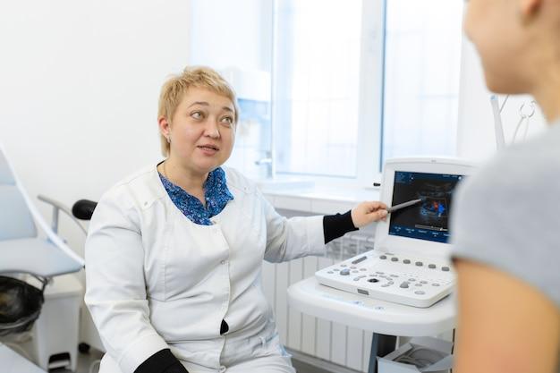 Lekarz doradza pacjentce po wykonaniu diagnostyki usg na monitorze