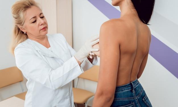 Lekarz dostaje zbadać piersi młodej kobiety.