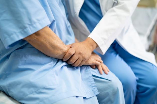 Lekarz dotykając rąk pacjent azjatycki starszy kobieta z miłością i troską.