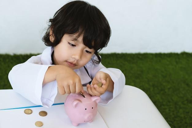 Lekarz dziecięcy i sprzęt medyczny z różową skarbonką oszczędzanie pieniędzy na koncepcję przyszłego planu