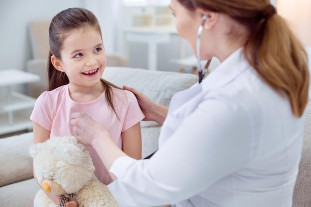 Lekarz dziecięcy. jowialna radosna dziewczyna śmiejąca się i obejmująca pluszowego misia, podczas gdy kobieta lekarz za pomocą stetoskopu
