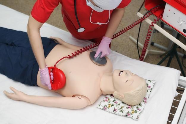 Lekarz dziewczyna defibryluje manekina lekarze egzaminu, ale resuscytacja w nagłych wypadkach. koncepcja ratowania życia