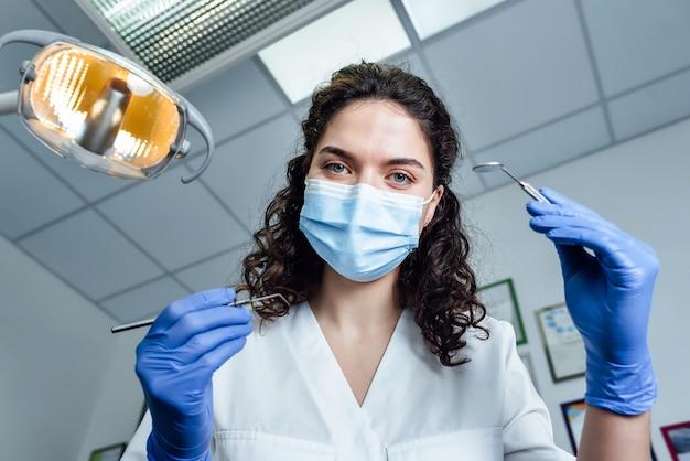 Lekarz dziewczyna trzyma narzędzia stomatologiczne w dłoniach i pochylił się nad pacjentem