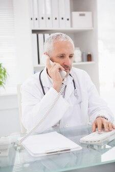 Lekarz dzwoniący i korzystający z komputera