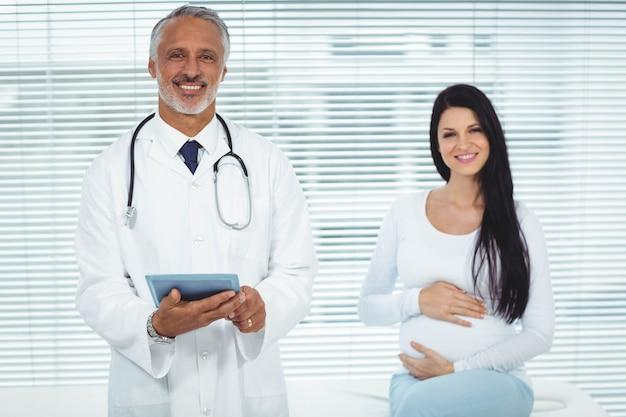 Lekarz i kobieta w ciąży uśmiecha się do kamery w klinice