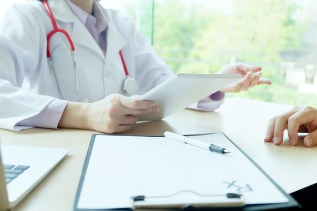 Lekarz i pacjent omawiają coś, tylko ręce przy stole