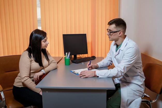 Lekarz i pacjent podczas konsultacji lekarskiej w gabinecie lekarskim. pojęcie opieki zdrowotnej.
