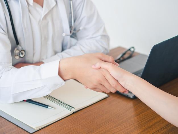 Lekarz i pacjent są drżenie ręki w szpitalu. opieka zdrowotna i medyczna koncepcja.