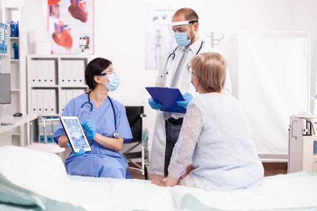 Lekarz i pielęgniarka przeprowadzający badanie starszego pacjenta noszącego maskę na twarz jako środek ostrożności w trakcie pandemii covid19