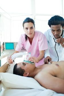 Lekarz i pielęgniarka reanimująca pacjenta płci męskiej