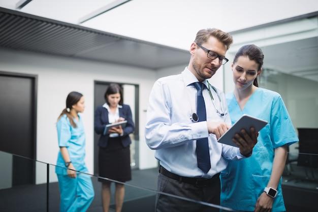Lekarz i pielęgniarka rozmawiają na cyfrowym tablecie