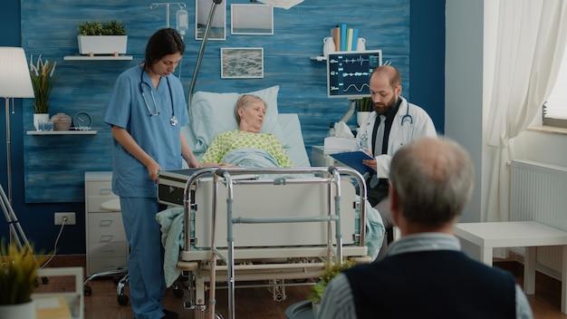 Lekarz i pielęgniarka udzielająca pomocy emerytowanej kobiecie