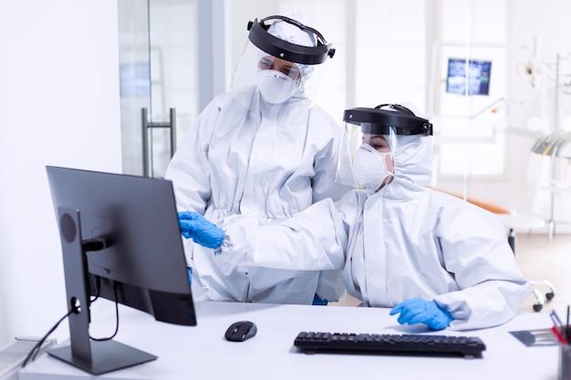Lekarz i pielęgniarka w kombinezonie ochronnym patrzący na monitor podczas globalnej pandemii z covid-19. zespół medyczny noszący sprzęt ochronny przed pandemią koronawirusa w recepcji stomatologicznej jako środek ostrożności.